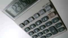 Pocket calculator falling on white surface Stock Footage