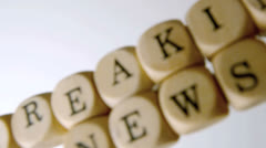 Breaking news spelled out in dice falling on white surface - stock footage