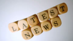 Latest news spelled out in dice falling on white surface Stock Footage