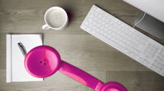 Pink phone receiver falling onto office desk Stock Footage