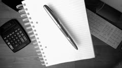 Fountain pen and notepad falling on office desk Stock Footage