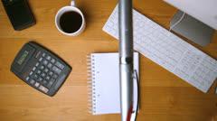 Fountain pen falling onto notepad on office desk Stock Footage