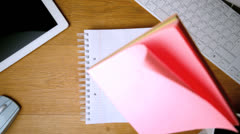 Pink post its falling on notepad on office desk Stock Footage