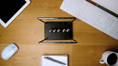 Overhead of newtons cradle toy on office desk Stock Footage