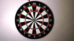 Dart hitting the dart board between two other darts - stock footage