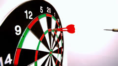 Dart hitting the dart board between two other darts side view - stock footage