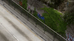 Graffiti and ivy covered wall along freeway Stock Footage