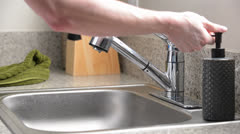 Man washes hands in kitchen sink and dries with green towel - stock footage
