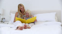 Mother and daughter reading storybook together Stock Footage