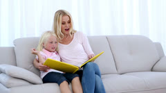 Mother and daughter reading a book together Stock Footage