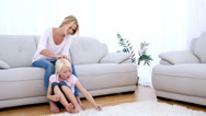 Mother playing with daughters blonde hair Stock Footage