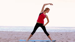 Woman stretching on the beach Stock Footage