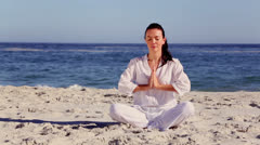 Brunette woman meditating in sukhasana pose Stock Footage
