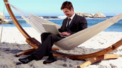 Businessman typing on his laptop in a hammock - stock footage