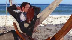 Buisnessman relaxing in hammock - stock footage