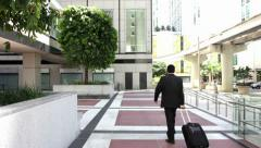 Young city businessman with travel luggage Stock Footage