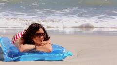 Girl sunbathing on a lilo on the beach Stock Footage