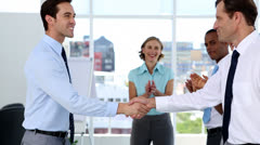 Businessmen shake hands while other business people applauding - stock footage