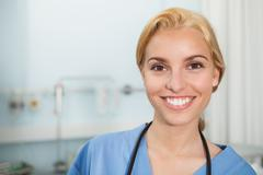 Front view of a nurse smiling while looking at camera Stock Photos