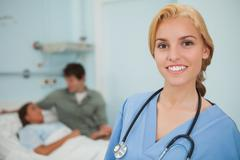 Stock Photo of Blonde nurse smiling next to a patient