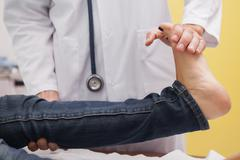 Doctor auscultating a patient ankle - stock photo