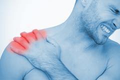 Man wincing in pain at shoulder pain - stock photo