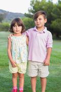 Cute brother and sister standing in the park Stock Photos