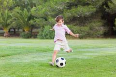 Little boy kicking his football - stock photo