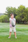 Little boy holding out rugby ball - stock photo