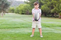 Smiling boy holding out rugby ball Stock Photos