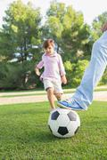 Father holding football down with foot with son running to kick it - stock photo