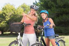 Mother pointing a route out to daughter on bikes Stock Photos