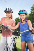 Stock Photo of Happy mother and daughter with their bikes