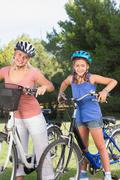 Stock Photo of Smiling mother and daugher with their bikes