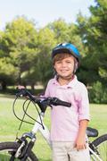 Happy little boy wearing a helmet with his bike - stock photo