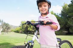 Cute boy wearing helmet and leaning on bike Stock Photos