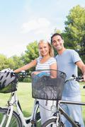 Stock Photo of Happy couple standing with their bikes