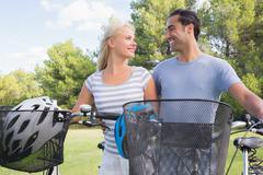 Stock Photo of Couple looking at each other with their bikes