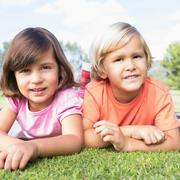 Smiling brother and sister lying on a blanket - stock photo