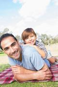 Portrait of father and son on picnic blanket Stock Photos