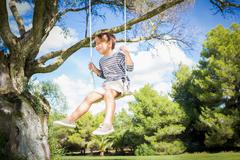 Cute boy swinging on swing hanging from tree - stock photo