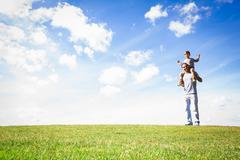 Isä antaa pojalle possu takaisin ratsastaa puistossa Kuvituskuvat