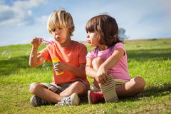 Brother and sister blowing bubbles Stock Photos