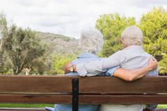 Elderly couple sitting on a park bench - stock photo