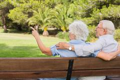 Elderly woman pointing something out to partner on park bench - stock photo