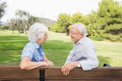 Couple chatting together on park bench - stock photo