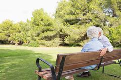 Elderly couple sitting on bench - stock photo