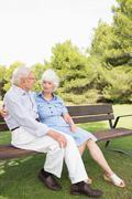 Elderly couple sitting on bench chatting - stock photo