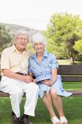 Portrait of elderly couple with digital tablet in the park - stock photo