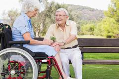 Elderly man giving his partner in a wheelchair a flower - stock photo
